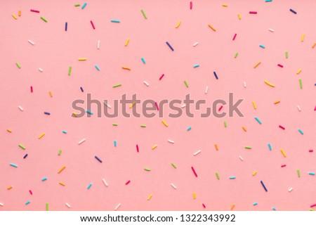 trendy pattern of colorful sprinkles for background of design banner, poster, flyer, card, postcard, cover, brochure over pink