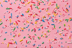 trendy pattern of colorful sprinkles over pink background, decoration for cake and bakery