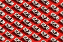 trendy pattern of white toy car model Ferrari on red background