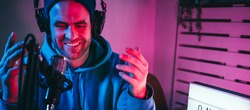 Trendy podcast creator streaming audio broadcast at his home studio using stylish cyber punk blue magenta ambient light