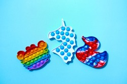 Trendy pop it and simpl dimple toys in form of crab, duck, and unicorn on blue background. Top view Flat lay