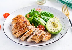 Trendy salad. Chicken grilled fillet with salad fresh tomatoes and avocado. Healthy food, ketogenic diet, diet lunch concept. Keto/Paleo diet menu.