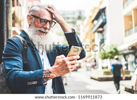 Trendy senior man using smartphone app in downtown center outdoor - Mature fashion male having fun with new trends technology - Tech and joyful elderly lifestyle concept - Focus on his face #1169911873