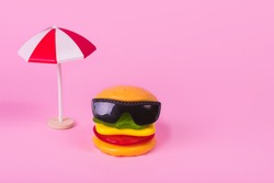 Trendy summer concept with fast food - hamburger in sunglasses and sun umbrella  on pastel pink background. Travel and vacation concept. Abstract food concept with gummy candies. Copy space