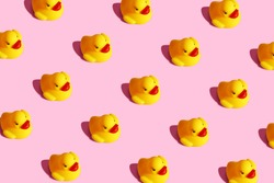 Trendy sunlight isometric view child yellow rubber duck toy wallpaper. Seamless still life seamless pattern on a pastel pink background. Minimal creative summer or kid concept banner poster website.
