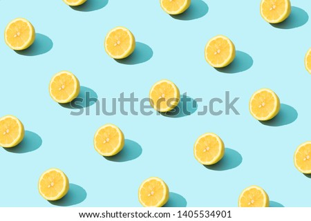Trendy sunlight Summer pattern made with yellow lemon slice on bright light blue background. Minimal summer concept.