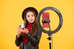 trendy teen girl blogger use selfie led lamp and smartphone on tripod for making online video tutorial beauty blog presenting makeup cosmetics, weblog.