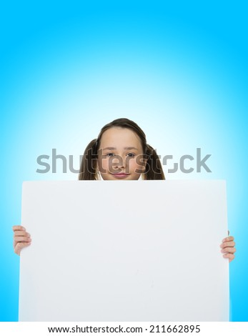 Trendy teenage girl holding to a blank card on blue background
