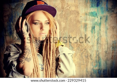 Trendy teenage girl with blonde dreadlocks listening to music on headphones. Jeans style. Modern generation. #229329415