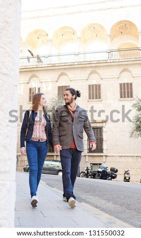 Trendy tourist couple walking passed classic architecture buildings in a destination city while on vacation, smiling and holding hands. - stock photo
