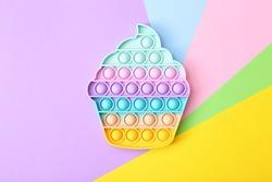 Trendy toy antistress, pop it on a rainbow background, fidget toy, top view