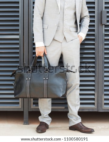Trendy trendy big handbag in the hands of a young businessman. Part of the body. Fashion. Outdoor. #1100580191