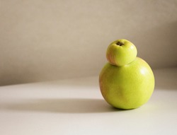 Trendy ugly food.Two Siamese apples joined together on a white table.Copy space with shadows.Funny, unnormal fruit or food waste concept.
