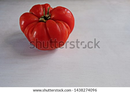 Trendy ugly organic produce  - one red tomato on white table with copy space for text.Horizontal orientation. Buying imperfect products is a way to deal with food waste #1438274096