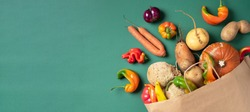 Trendy ugly organic vegetables. Assortment of fresh eggplant, onion, carrot, zucchini, potatoes, pumpkin, pepper in craft paper bag over green background. Top view. Cooking ugly food concept. Non gmo