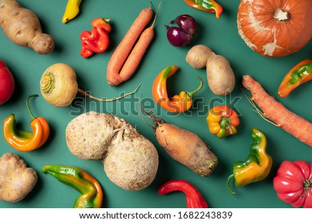 Trendy ugly organic vegetables. Assortment of fresh eggplant, onion, carrot, zucchini, potatoes, pumpkin, pepper in craft paper bag over green background. Top view. Cooking ugly food concept. Non gmo Foto stock ©