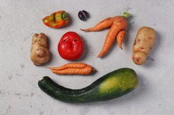Trendy Ugly Organic Vegetables: potatoes, carrots, tomato, pepper, zucchini and plum on gray background, ugly food concept, top view