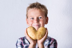 Trendy ugly vegetable, funny potato with imperfect heart shape in hands. Farmers produce, organic, misshapen weird food waste concept. Top view, copy space background