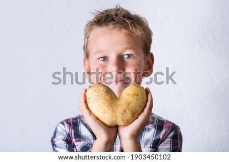 Trendy ugly vegetable, funny potato with imperfect heart shape in hands. Farmers produce, organic, misshapen weird food waste concept. Top view, copy space background Foto stock ©