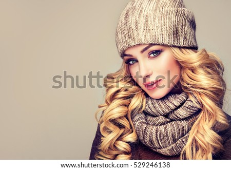 trendy warm winter - beautiful  young blonde  woman in gray wool winter hat and scarf smiling .  Portrait of beauty  winter girl  in knitted  woolen  clothing hat and scarf  Snood . #529246138