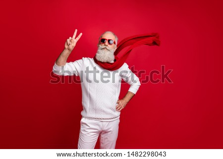 Trendy well-dressed santa character style showing v-sign wear sun specs knitted clothes isolated red background