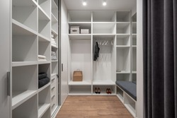 Trendy white dressing room with luminous lamps and a parquet on the floor. There are lockers, shelves and hangers with clothing, shoes, tall mirror, soft seat with niches, gray curtains. Horizontal.