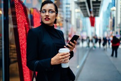 Trendy woman in classy outfit standing near glass wall and browsing smartphone while holding cup of coffee and looking away