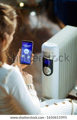 Trendy woman in white sweater and skirt in the modern living room in sunny winter day sitting near couch and white electric oil radiator using smartphone app for temperature control.