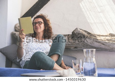 Trendy woman relaxing outdoor reading a book after working with laptop. Day off after work happy girl read a blast in the patio. Relax time on holiday travel. Carefree happiness healthy female concept