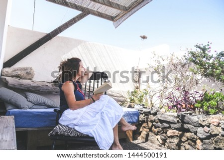 Trendy woman relaxing outdoor reading a book in a rural back yard. Day off after work happy girl read a blast in the patio. Relax time on holiday travel. Carefree happiness healthy female concept