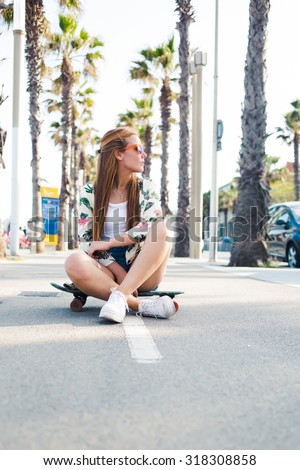 Trendy woman skater in colorful sunglasses sitting on her skateboard on tropical lane with copy space, young hipster girl dressed in stylish clothing resting after riding during free weekend time stock photo