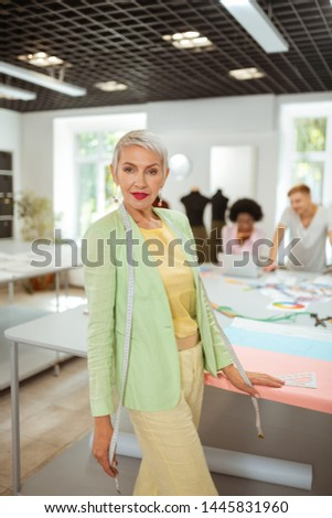 Trendy woman. Trendy senior fashion designer with a measuring tape on her shoulders standing in a studio #1445831960