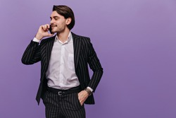 Trendy young boy with brunette hair, light shirt and classic striped suit, putting one hand in pocket, talking on mobile phone and looking aside. Business concept isolated over violet background