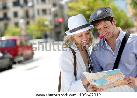 Trendy young couple in town with touristic map