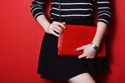 Trendy young girl in black skirt and striped shirt holding red leather handbag red background