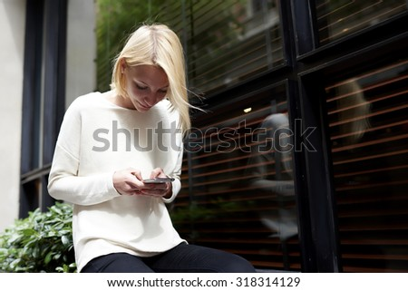 Trendy young woman focused chatting or talk on smart phone near blank copy space background for your content or text message, female hipster student using mobile phone for connect to wireless outdoors