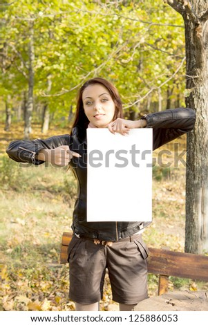 Trendy young woman in shorts holding up a blank sign and pointing to it with her finger while standing alongside a bench in woodland