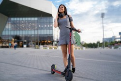 Trendy young woman in the city with her e scooter