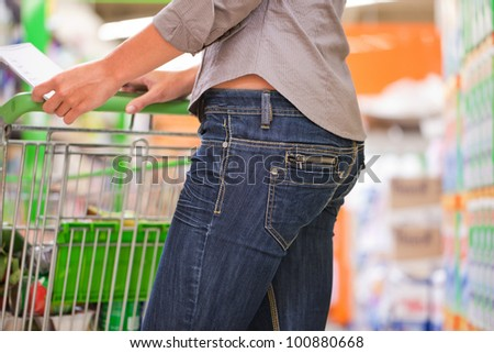 Trendy young woman shopping with trolley at supermarket