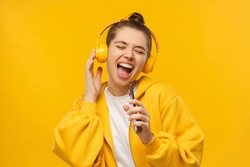Trendy young woman singing favorite song out loud in phone as mic, wearing wireless headphones, isolated on yellow background. Karaoke online app