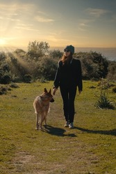 Trendy young woman walking her German Shepherd dog at sunset at the coast with ocean backdrop and sunburst in an active outdoors lifestyle concept