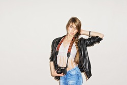Trendy young woman with vintage film camera wearing crochet fringe top, black leather jacket and denim jeans posing. Studio shot, horizontal, closeup, retouched, matte filter applied, copy space.