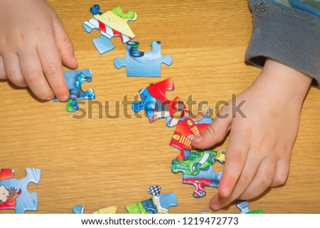 TRENTO, Italy - October 20, 2018: Baby hands assemble the puzzle on the table #1219472773