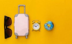 Trevel flat lay. Mini luggage and alarm clock, sunglasses, and globe on yellow background. Time to travel. Top view