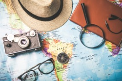 Treveling concept. Hat,Vintage camera with compsss and eye glasses on world map background.