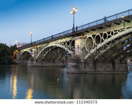 Triana Bridge, the oldest bridge of Seville, Spain at dusk