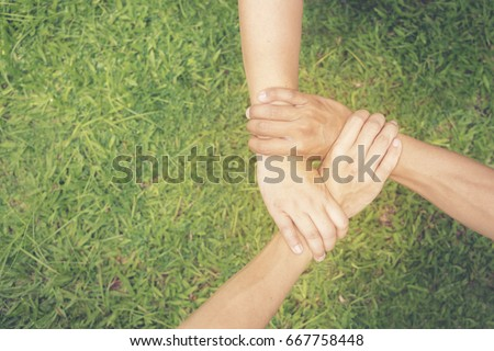 Triangle hands of trust partners. Close up hands together of Team Businessman agreement over green grasses background to unified powerful with copy space.Trust business in authentic of people concept #667758448