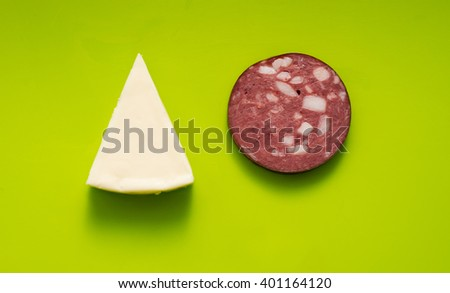triangle of cheese and a slice of sausage #401164120