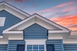 Triangle shape decorative gable with colonial white soffit and fascia on a blue horizontal vinyl siding modern American estate home with colorful dramatic orange sunset sky