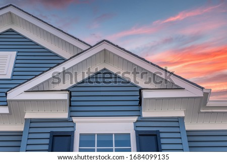 Triangle shape decorative gable with colonial white soffit and fascia on a blue horizontal vinyl siding modern American estate home with colorful dramatic orange sunset sky Stock photo ©